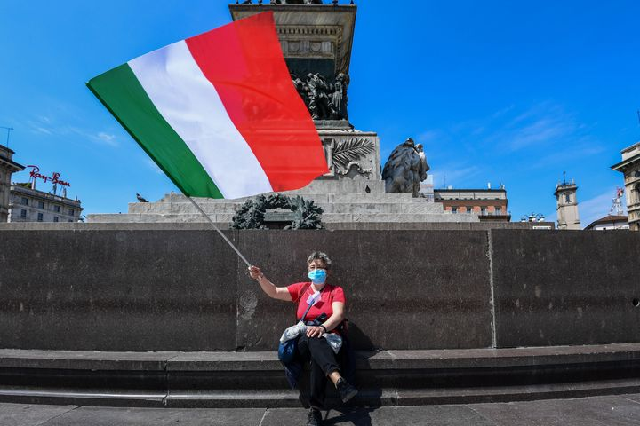 A woman waves the Italian flag in Milan on Monday as Italy starts to ease lockdown measures.