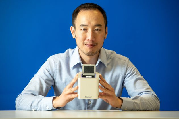 Spartan Bioscience CEO Paul Lem holds one of his company's portable, rapid testing devices used to detect...