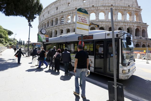 ROME, ITALY, MAY 04: Passengers approach a bus at a stop in front of the Colosseum in Rome, Italy, on...
