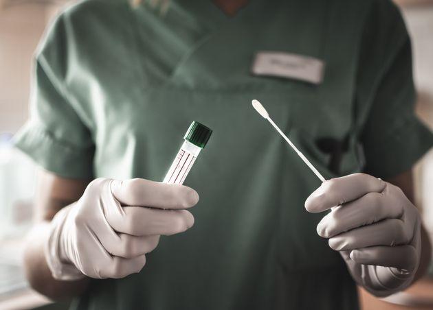 nurse holds a swab for the coronavirus / covid19