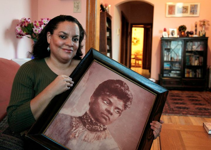 Michelle Duster, great-granddaughter of the civil rights pioneer, holds a portrait of Wells in her home in Chicago's South Si