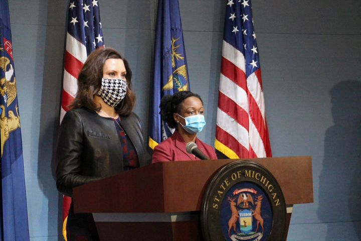 Michigan Governor Gretchen Whitmer, left, wears a mask while addressing the state on Friday.