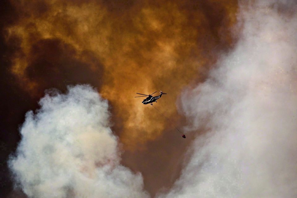 A helicopter battles a wildfire in Fort McMurray, Alta., on May 4,