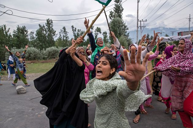 Women shout slogans as policemen fire teargas and live ammunition in the air to stop a protest march...