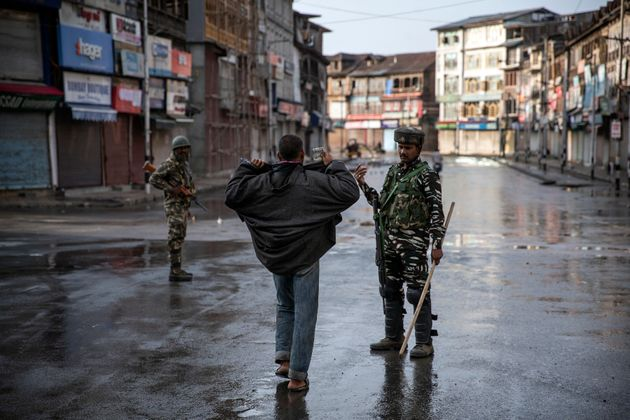 An paramilitary soldier orders a Kashmiri to open his jacket before frisking him during curfew in Srinagar,...