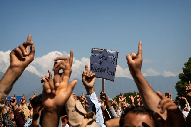 Kashmiri men shout freedom slogans during a protest against the abrogation of Article 370 after Friday...