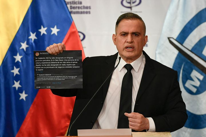 Venezuela's Attorney General Tarek William Saab holds up Twitter posts during a press conference regarding what the governmen