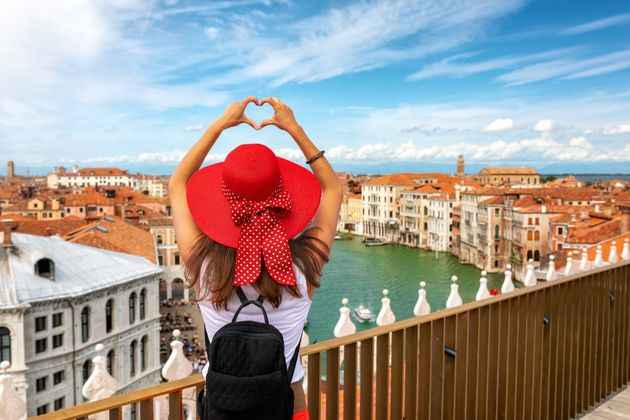 Happy, female traveler tourist shapes a heart with her hands over the skyline of Venice, Italy, during...