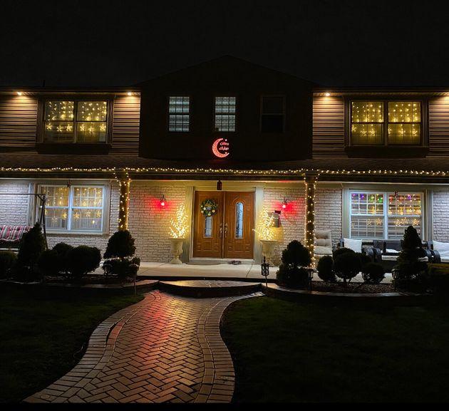Una luna creciente que cambia de color cuelga fuera de la casa de una familia como parte de su concurso de luces de Ramadán