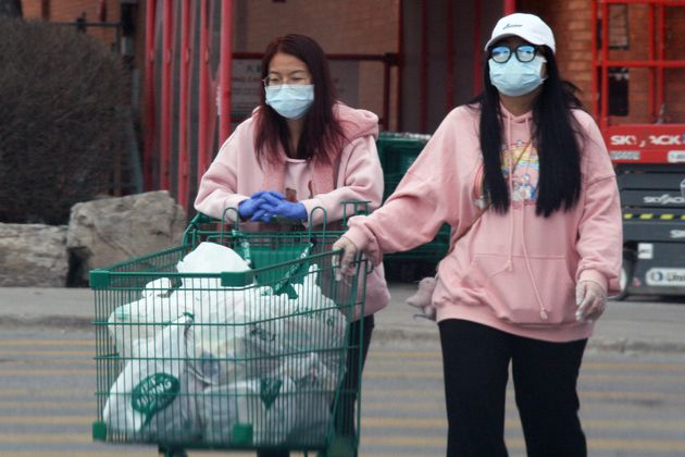 People wear face masks and surgical gloves for protection while grocery shopping in Toronto on April...