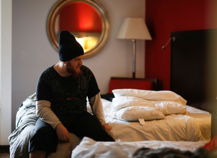 Travis Johnson sits on his bed in his room at the Red Lion Hotel, one of Downtown Emergency Service Center's temporary shelte