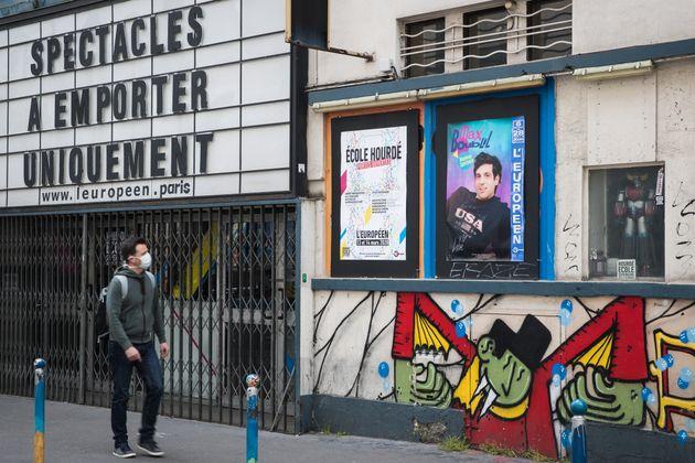 Pendant le confinement, un homme passe devant la salle de spectacles L'Européen à Paris, qui précise...