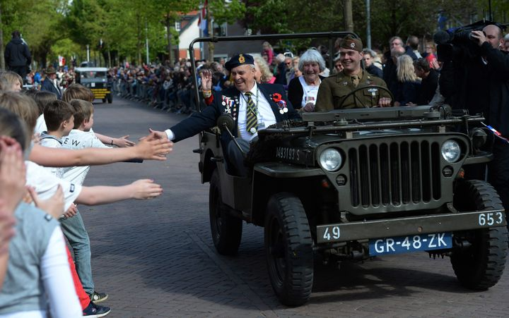 Children reach out to touch the hand of Canadian World War II navy veteran Bert Reynolds, 88,  as he takes part in a parade to celebrate the 70th anniversary of the Liberation of the Netherlands in Wageningen, Netherlands on Tuesday, May 5, 2015.  (Sean Kilpatrick/The Canadian Press via AP) MANDATORY CREDIT