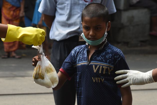 A child receives food during a meal distribution in Kolkata's College Street on May 4,
