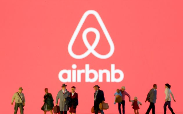 Small toy figures are seen in front of diplayed Airbnb logo in this illustration taken March 19, 2020....