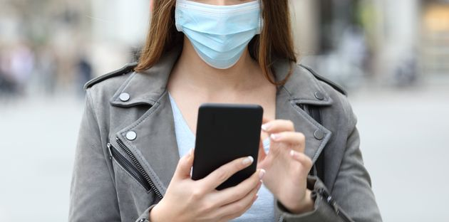 Front view portrait of a serious young girl with protective mask checking her smart phone on a city