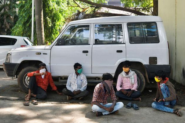 Migrant workers wait for transportation to leave for their hometowns in Bengaluru on April 30,