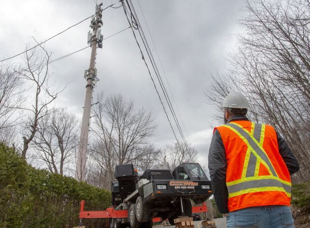 A cellphone tower is repaired by technicians in Piedmont, Que., after a fire was reported on