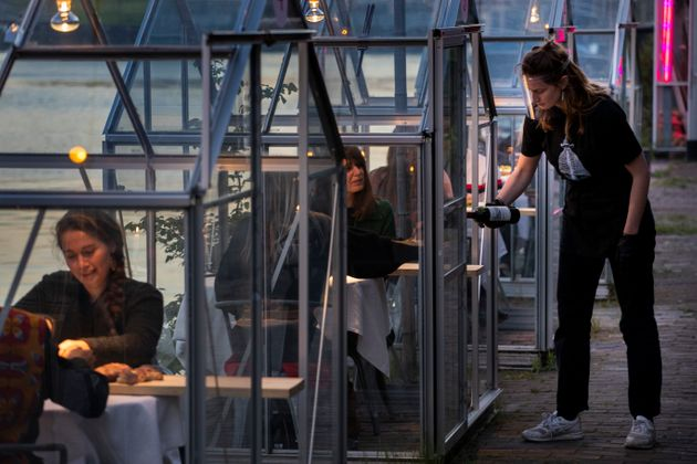 Staff at the Mediamatic restaurant serve food to volunteers seated in small glasshouses during a try-out...