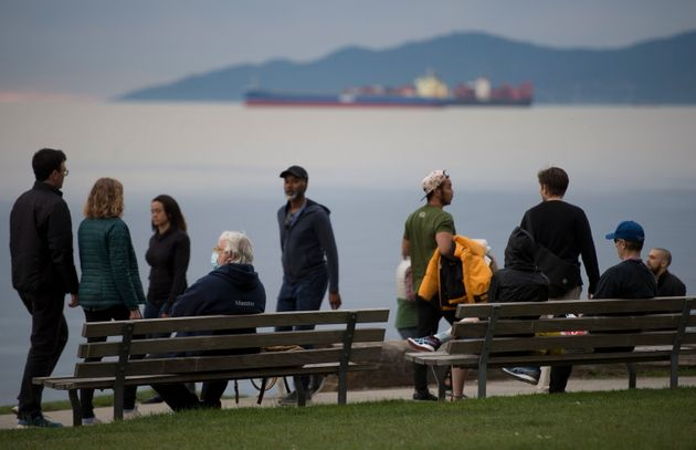 People are seen walking along the seawall in English Bay in Vancouver on May 4,
