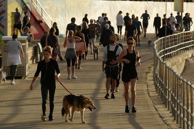 People walk and jog at the walk side of Bondi Beach after the beach reopens to surfers and swimmers after...