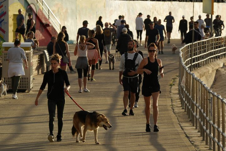 People walk and jog at the walk side of Bondi Beach after the beach reopens to surfers and swimmers after it was closed to curb the spread of the coronavirus disease (COVID-19), with strict social distancing measures remaining in place, in Sydney, Australia, April 28, 2020.  REUTERS/Loren Elliott