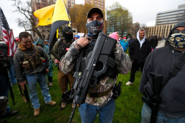 A protester carries his rifle at the State Capitol in Lansing, Mich., Thursday, April 30, 2020. (AP Photo/Paul Sancya)
