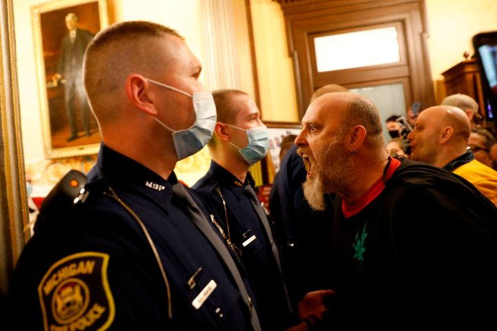 Protestors try to enter the Michigan House of Representative chamber and are being kept out by the Michigan State Police on A