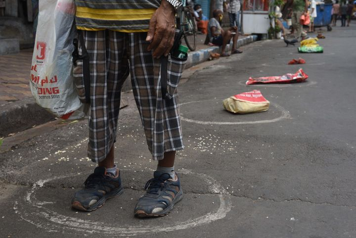 Bags kept as placeholders in circles marking social distance in a queue to collect essential food grains from a fair price shop in Entally on May 5, 2020 in Kolkata, India.