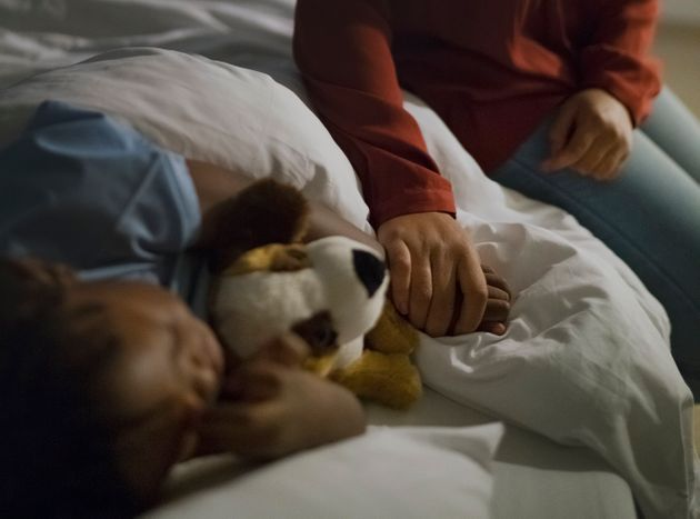Midsection of woman holding son's hand sleeping on hospital bed. Ill boy is with stuffed toy relaxing...