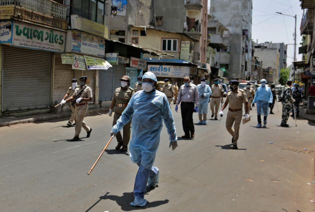 Police officials patrol a street during lockdown in Ahmedabad on April 19,