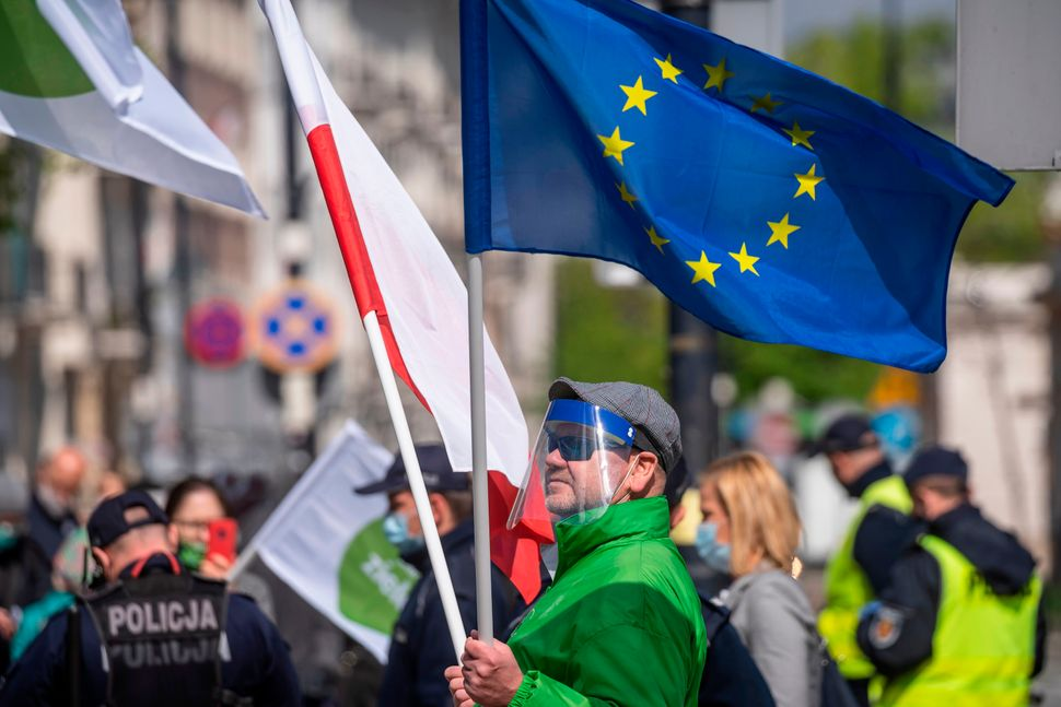A man holds a Polish and an European flag during a demonstration outside parliament, on May 7, 2020 in Warsaw.
