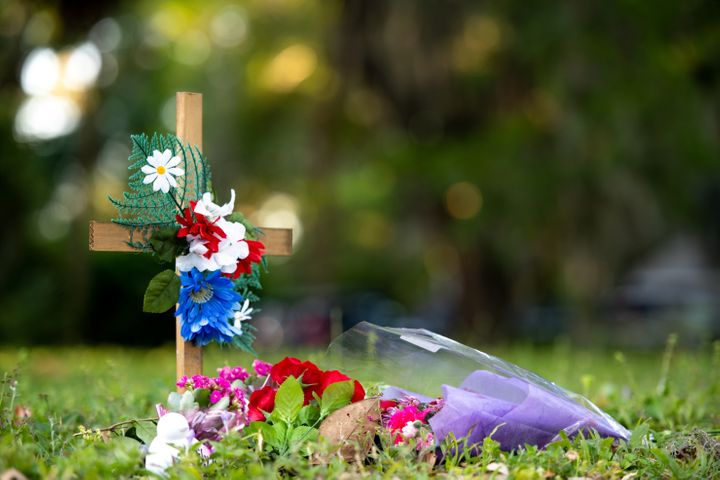 A cross with flowers sits near the intersection of Satilla Rd. and Holmes Rd. in the Satilla Shores neighborhood where Ahmaud