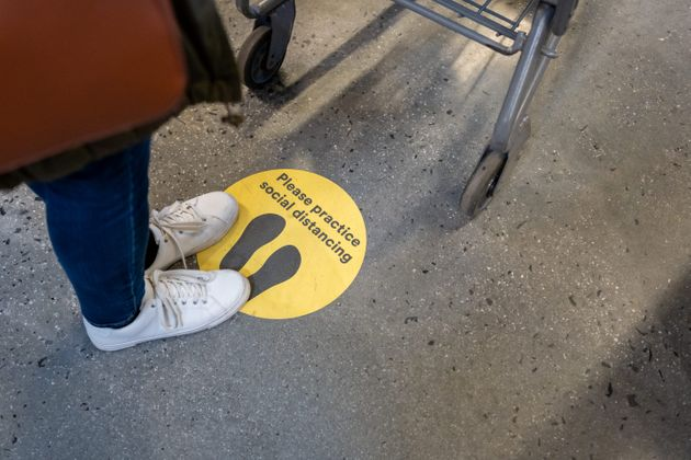 A sign on the floor of a supermarket reminding shoppers to stay