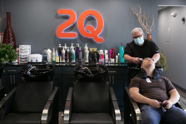 Harris Little washes Matt Kim's hair at 2Qute Hair Salon on April 27, 2020, in Atlanta. Georgia Gov. Brian Kemp has allowed s