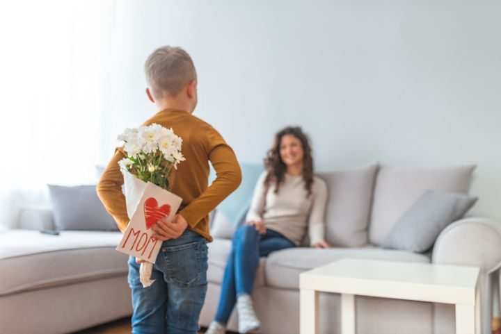 Happy mother's day! Child son congratulates moms and gives her a postcard. Child boy congratulates mother and gives a bouquet of flowers and gift
