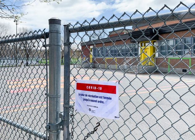A COVID-19 sign is shown on a gate at a school in Montreal on May 5,