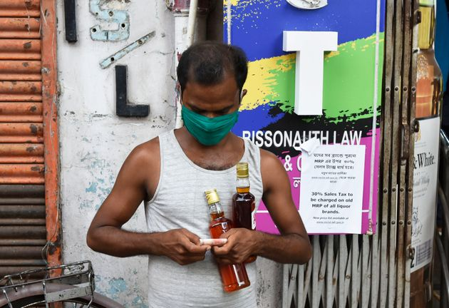 A man buys alcohol from a shop in Kolkata during the Covid-19 lockdown on May 7,