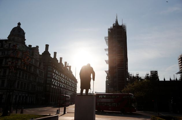 The statue of Britain's wartime Prime Minister Winston Churchill stands in an almost empty Parliament...