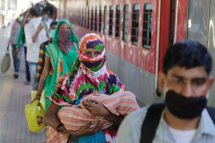 Migrant workers stand to board a special train to return to Agra, Uttar Pradesh, during a nationwide lockdown to curb the spread of new coronavirus, at a railway station in Ahmedabad, Gujarat, Saturday, May 2, 2020.