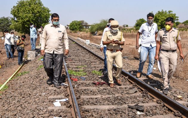 Police personnel along with officials walk on a rail track as they check the site following a train accident...