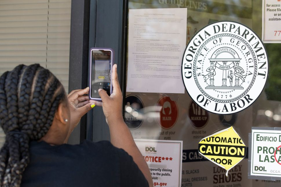 Arnashia McCain uses her phone to copy phone numbers posted on the locked doors of a Georgia Department of Labor office, May
