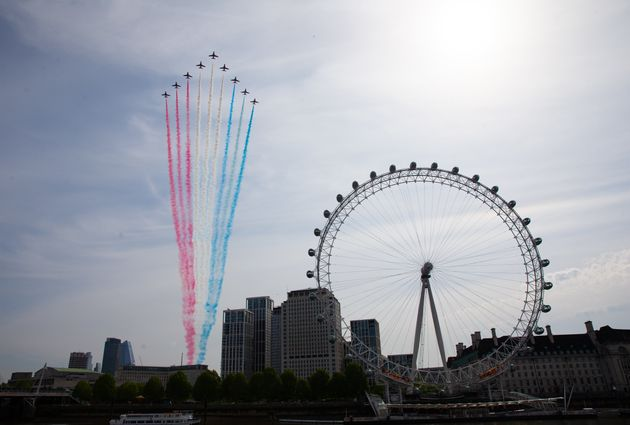 The Royal Air Force Red Arrows pass over the London Eye on the bank of the River Thames during a flypast...