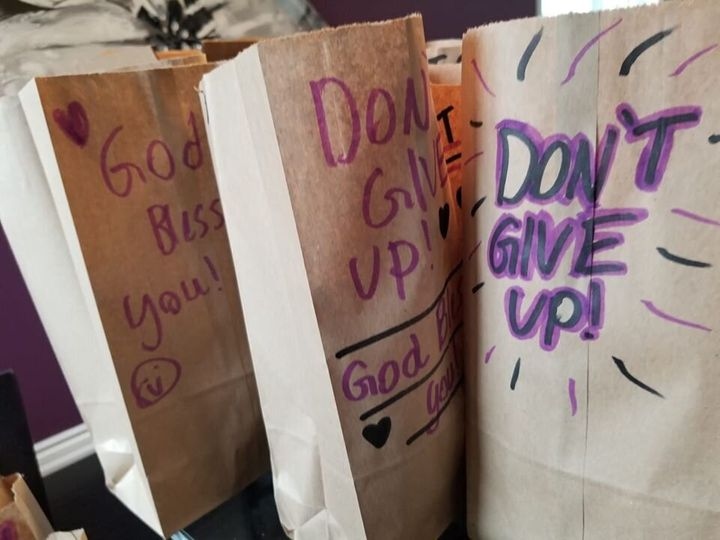 Antone's kids write inspiring messages on paper bags holding meals for recipients.