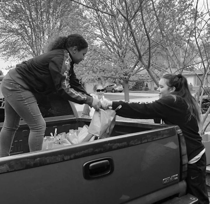 Antone's eldest daughters Hope and Shoshannah help their dad load supplies in his pickup truck.