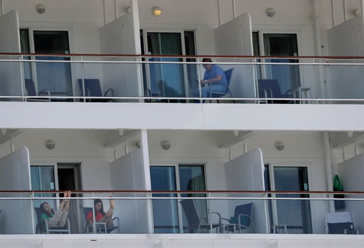 In this May 8, 2020 photo, people aboard the Norwegian Epic cruise ship docked at PortMiami in Miami, sit on their balconies.