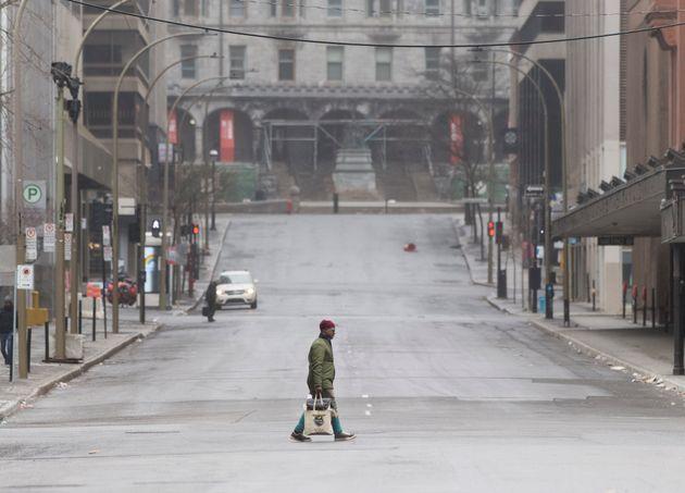 People cross an empty street in downtown Montreal on Apr. 5,