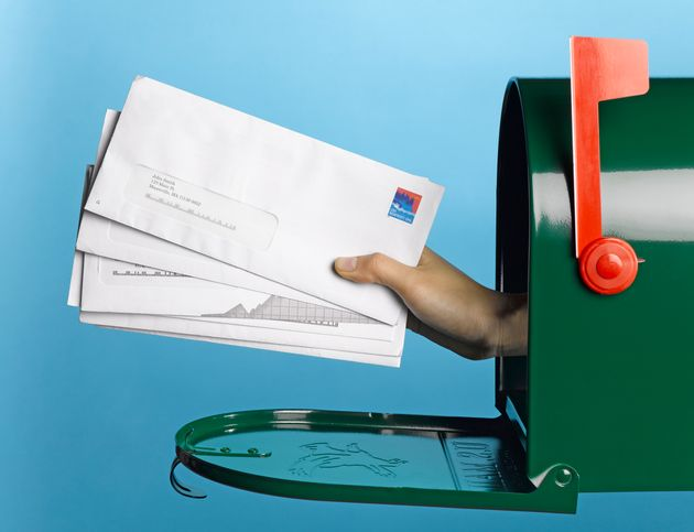 Young woman holding mail out of mailbox, side