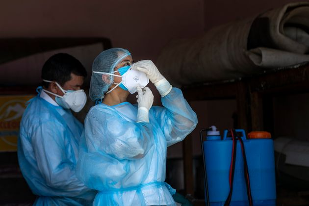 A doctor wears her protective mask before collecting samples from people to be tested for the coronavirus...