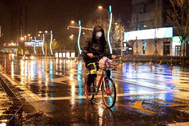 Un homme portant un masque facial fait du vélo dans une rue vide de Wuhan, dans la province centrale...